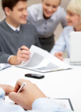 Foto de manos humanas haciendo notas sobre fondo de hombre explicando la idea a los empleados