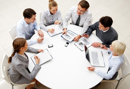 interacting: Image of company of successful partners discussing business plan at meeting