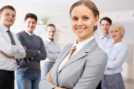 Portrait of confident business people looking at camera with pretty woman in front photo
