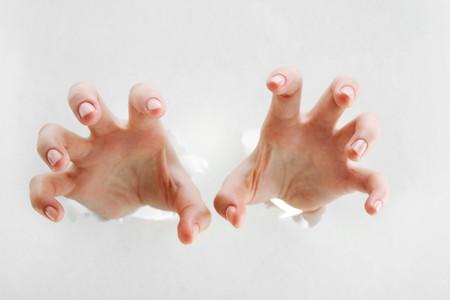 Imagen de manos humanas hace un gesto aterrador a través de papel rasgado  Foto de archivo
