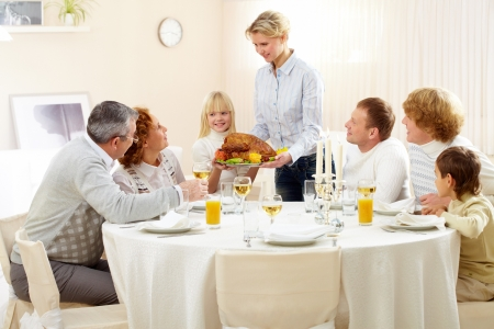 Portrait of big family sitting at festive table and looking at pretty woman with roasted turkey Stock Photo - 8228935