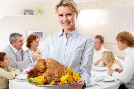 beautiful thanksgiving: Portrait of pretty woman with roasted turkey on background of happy family