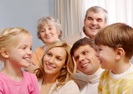 Portrait of boy and girl looking at each other with their parents and grandparents on background Stock Photo - 8228898