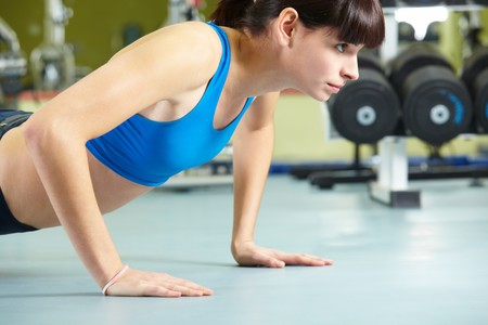 Photo of young girl doing difficult exercise for arm biceps on the floor Stock Photo - 8228997