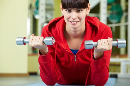 Portrait of young female with dumbbells doing exercises in gym Stock Photo - 8229006