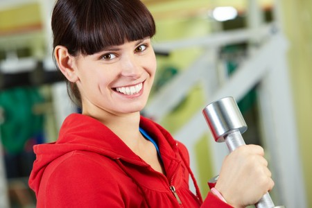 Portrait of young female with dumbbell doing exercises in gym Stock Photo - 8229011