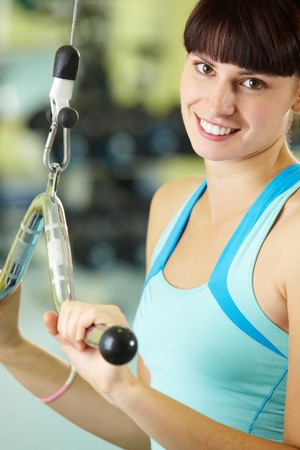 Photo of happy girl pumping muscles on special equipment photo