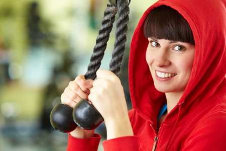 Photo of happy girl doing physical exercise on special equipment photo