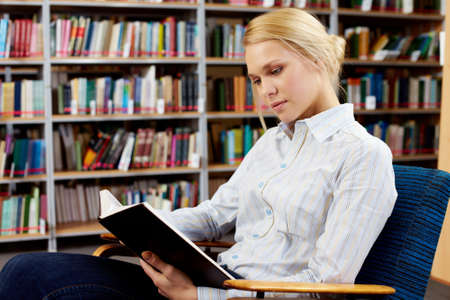 Portrait of clever student with open book reading it in college library Stock Photo - 8229005