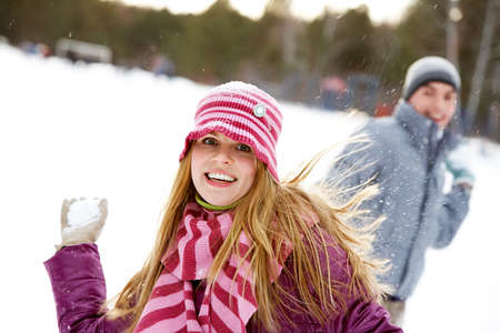 Image of attractive young woman before throwing snowball  photo