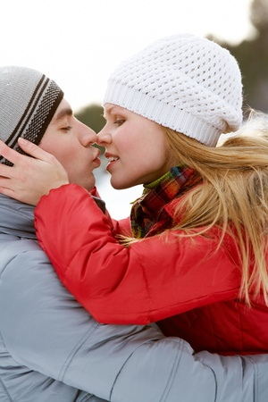 Portrait of happy couple kissing outdoors in winter  photo