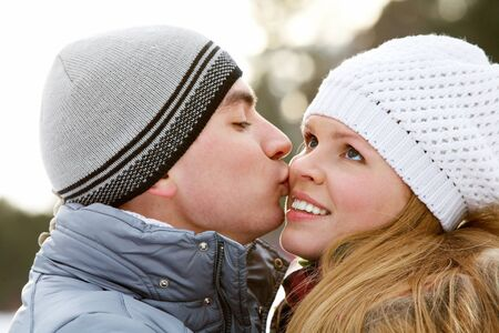 Portrait of happy young man kissing beautiful woman in winter Stock Photo - 8229245