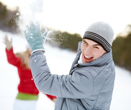 Image of attractive young man laughing while under snowball bombing photo