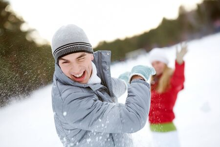 Image of attractive young man laughing during snowball play photo