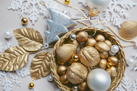 bedeck: Golden nuts, shell, beads and white ball lying in the basket on the christmas backdrop