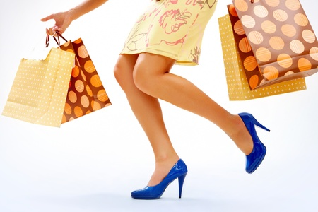 Legs of shopper in high-heeled shoes with colorful paper bags in move Stock Photo - 8229322