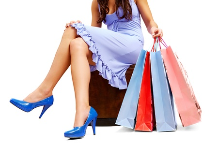 Legs of lady sitting and holding colorful paper bags Stock Photo - 8229319