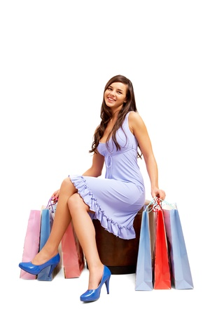 Happy shopper sitting and holding colorful paper bags Stock Photo - 8229313