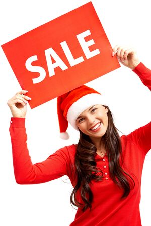 Happy girl in Santa cap holds card with symbol of sale photo