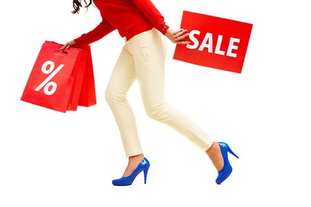 Legs of lady with red paper bags and sale card in move photo