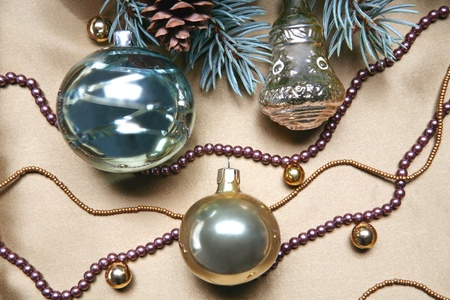 Christmas composition: glassy balls, beads and part of a Christmas twig with fir cone photo