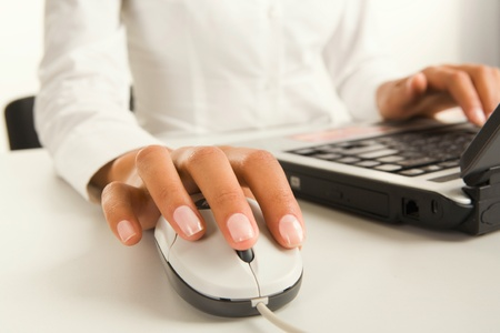 Woman�s hands touching computer mouse and keys of black opened laptop photo