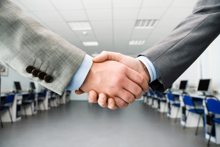 agreement: Image of shaking hands making an agreement in the classroom Stock Photo