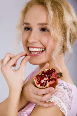 Portrait of a beautiful blonde woman with the pomegranate in her hand photo