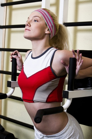 Young woman goes in for sport using the training simulator photo