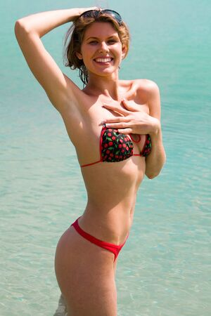 Portrait of beautiful woman in a bikini on a background of a water photo