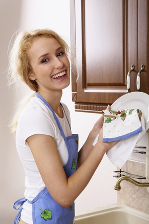 washing dishes: Smiling girl in the apron drying the dishes Stock Photo