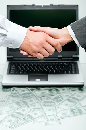 negotiate: Business person shaking hands over opened laptop and heaps of money on the background