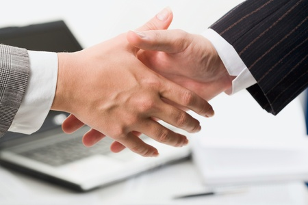 agreement: Close up of a business hands reaching for a handshake in the office