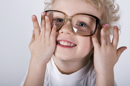 prank: Isolated on white curly smiling blond boy wearing big glasses