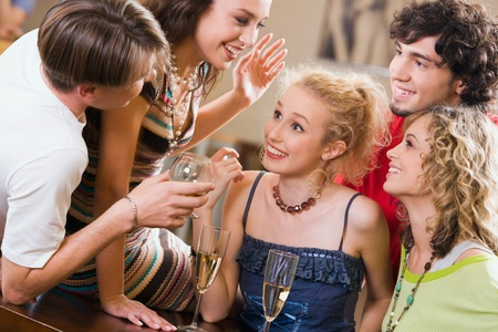 interacting: Young people are chatting at an evening-party
