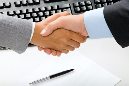 mani che si stringono: Uomo e donna agitando le mani su carta e penna, tastiera sullo sfondo