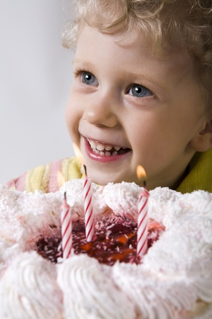 Happy curly blond boy with birthday cake going to blow out the candles photo