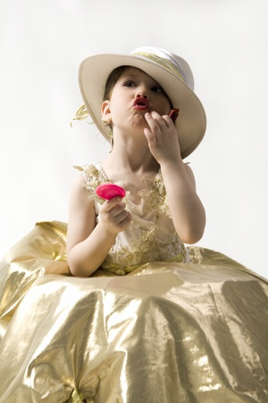Isolated on white sweet brunette little girl in light goldish dress and white hat making up her lips photo