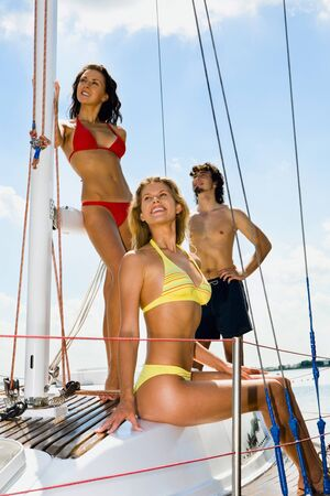 Portrait of three happy people having a rest on a yacht photo