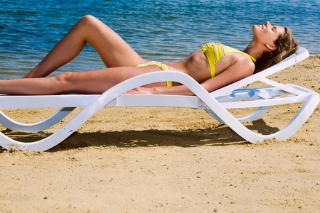 Portrait of attractive woman lying on a deck-chair  photo