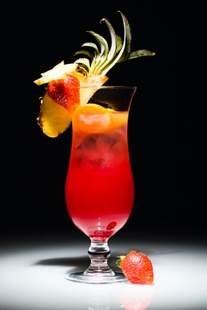 Photo of alcoholic cocktail with strawberry and piece of pineapple photo