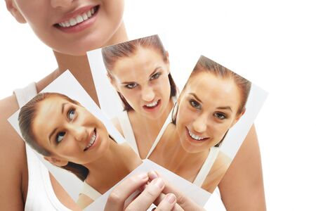 Close-up of young female holding three images of herself photo