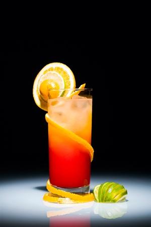 coctel de frutas: Tequila sunrise cóctel con rodaja de naranja y limón