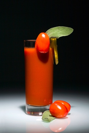 Bloody Mary cocktail in glass with tomatoes and slice of lemon isolated on the black background photo