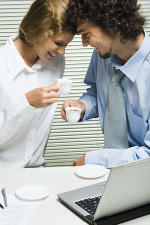 Pretty woman and smiling man drink the tea at the table in the office photo