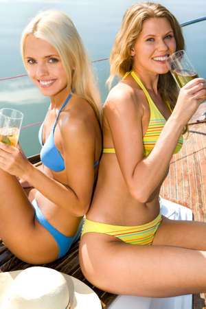 Portrait of two pretty women in swimwear drinking the cocktails  photo