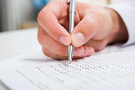 cuadro sinoptico: Mano masculina est� escribiendo en el documento de negocio acostado en la tabla