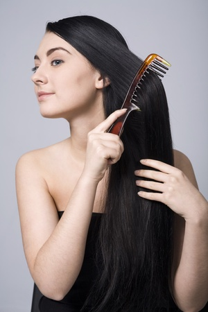 Sexual woman doing her long dark hair with intimacy photo
