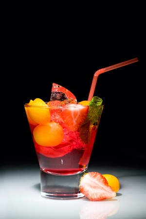 Purple dreams cocktail: mixed alcoholic drinks, small orange, strawberry, ice, leaf photo