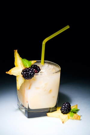 Snow ball cocktail with blackberries and pieces of pineapple photo